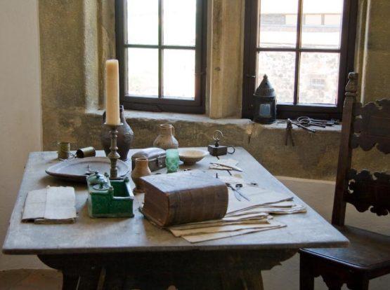 alter Tisch mit Bücher und Kerze