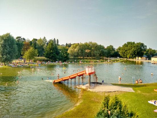 Eine Rutsche führt in das Naturbad Mockritz. Im und neben dem Wasser befinden sich Menschen