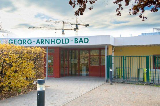 Die Frontansicht des Georg-Arnhold-Bads. Im Hintergrund ist der blaue Himmel und Kräne zu sehen