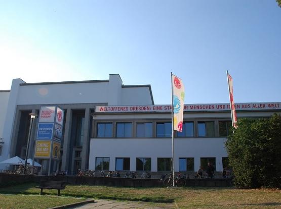 Man sieht die Vorderansicht des Deutschen Hygiene Museums. Es gibt zwei Fahnenmaste. Vor dem Gebäude stehen viele Fahrräder.